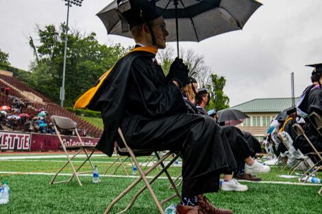 senior sits with umbrella on Fisher Field