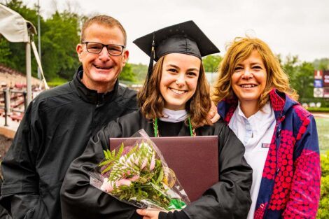 senior smiles with parents at commencement 2021