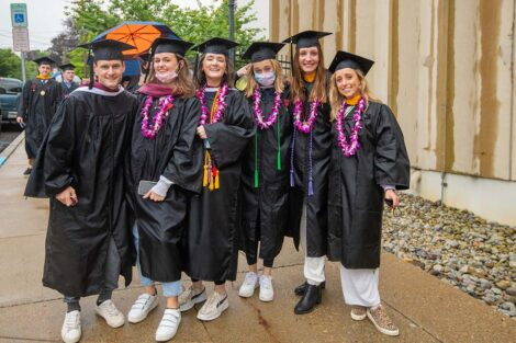 seniors in caps and gowns outside Kirby Sports Center