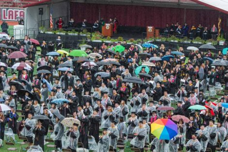 seniors in ponchos face the Fisher stadium stands Commencement 2021