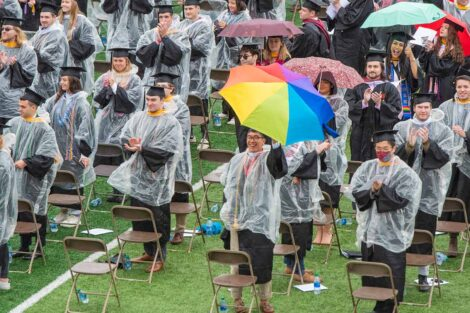 seniors in ponchos with umbrellas Fisher Field