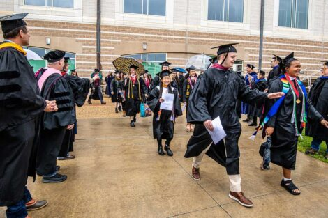 seniors smile as they walk toward Fisher Field in caps and gowns