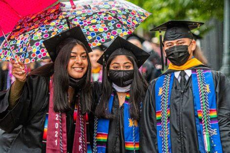 seniors smile with umbrellas pre-Commencement 2021