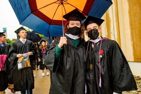 seniors smiling pre-Commencement with umbrellas