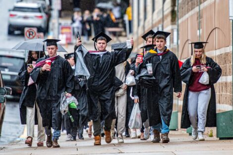 students walking into Kirby in caps gown