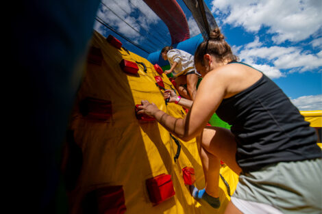 A student makes their way through an inflatable obstacle course.