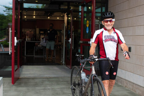 man in Lafayette cycling gear leaves College store walking with bike