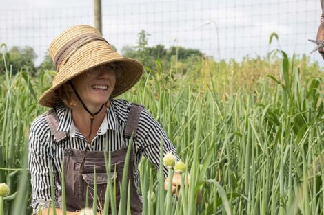 Lisa Miskelly smiles, surrounded by scallions.