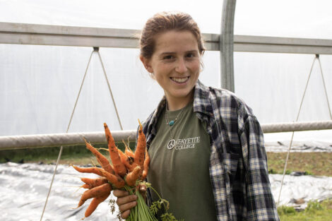 A student smiles, holding freshly picked carrots.