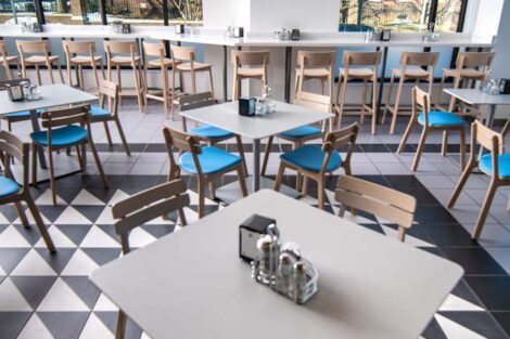 interior of Trolley Stop, tables, blue chairs, black and white floor