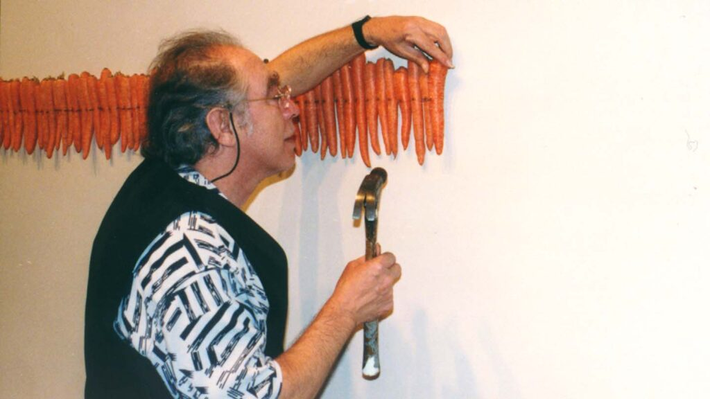 Artist holding hammer nails carrots to the wall