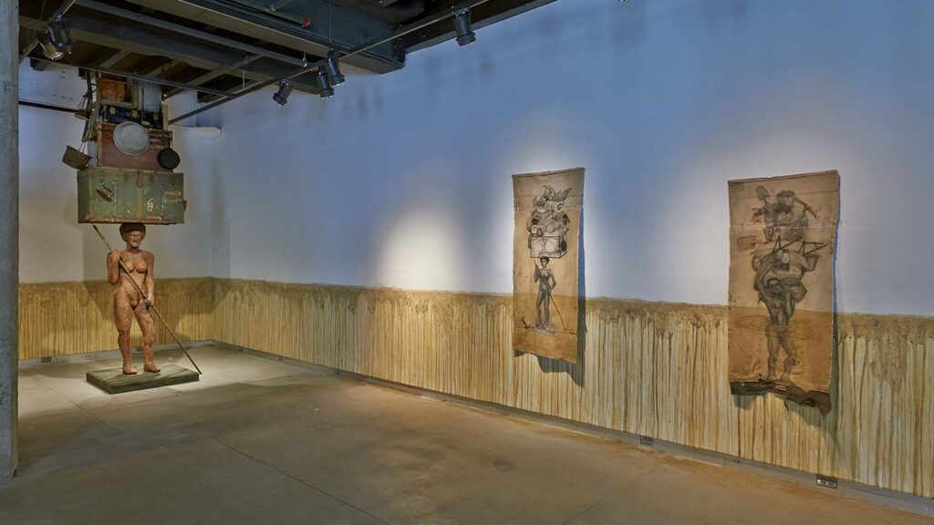 Mud marks the walls in the gallery around a hanging works and a statue on the floor