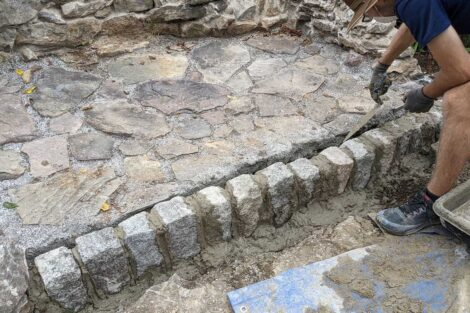 A rock wall at the front of the fire pit is set in mortar