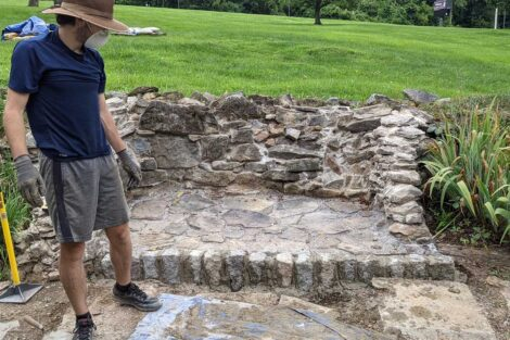 Student stands before the nearly final fire pit