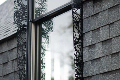 Laser cut shutters pattern the outside of a window