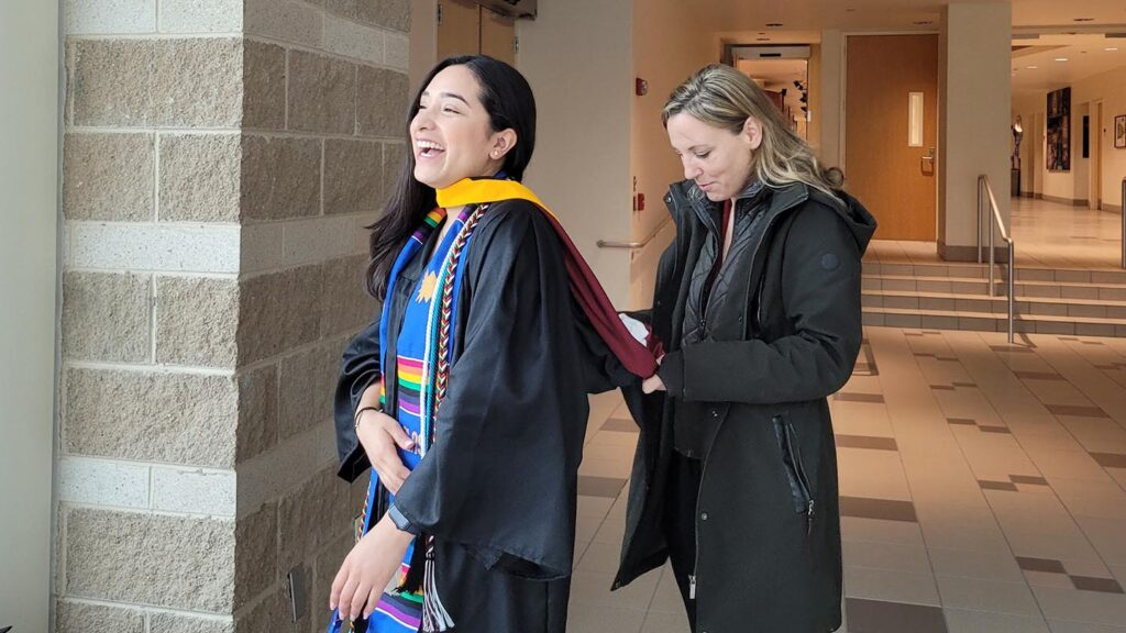Lisa Gabel helps Karla Cariño get ready for Commencement