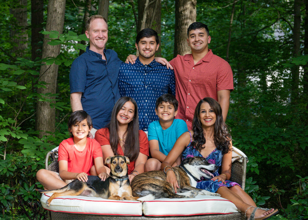 Tanuja Dehne '93 poses with her husband, Phillip Dehne '93, and their five children in front of a backdrop of greenery