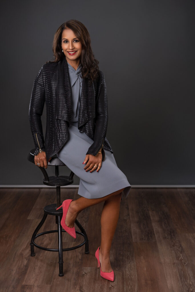 Trustee Tanuja Dehne '93 sits on a stool and smiles