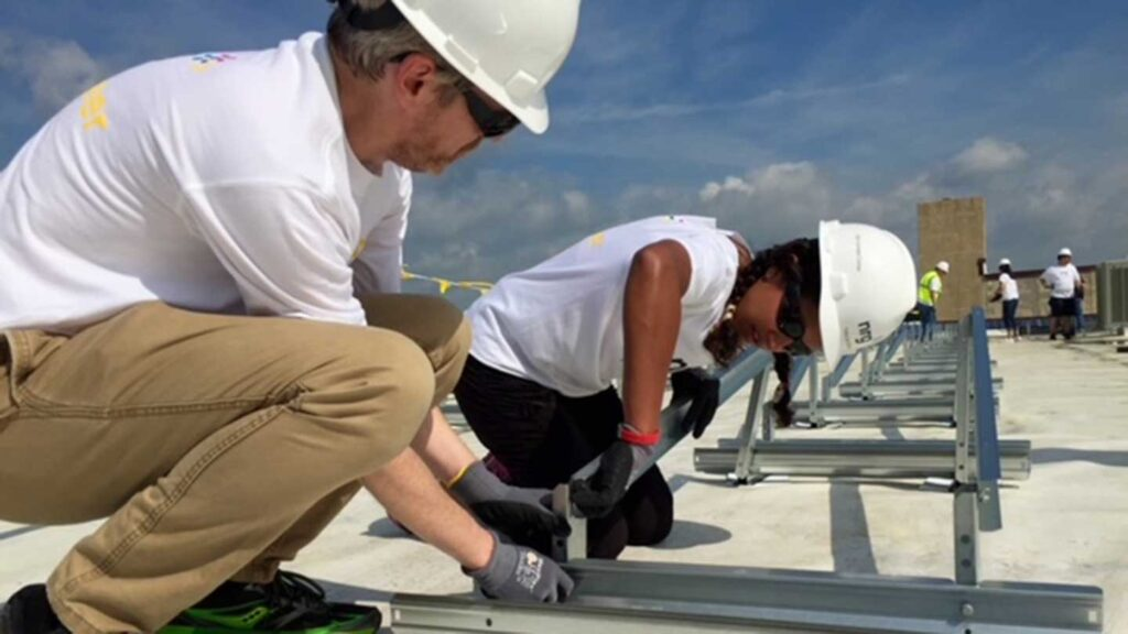 Lafayette trustee Tanuja Dehne '93 installing solar panels on the roof of HomeFront's Family Campus in Ewing, N.J., with NRG Energy