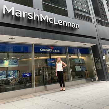 Student stands on NYC sidewalk below logo for Marsh McLennan