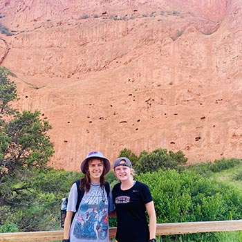 Two students in harts and t-shirts stand before red rock wall