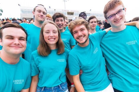 students in matching blue Tshirts smile in Fisher Field stands