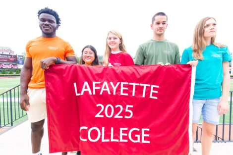 five students hold Lafayette College 2025 banner with Fisher Field in background