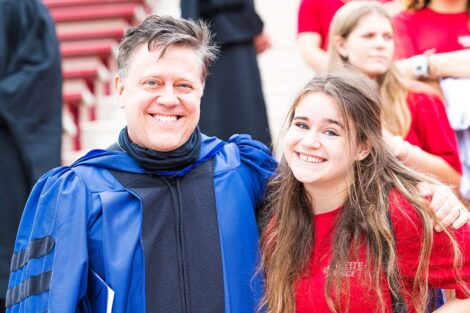 Professor Jim Dearworth wears robe, stands with daughter in red Tshirt smile