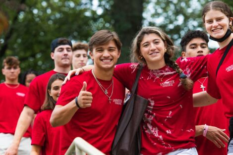 students in matching red Tshirts smile and give thumbs up