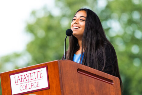 student government president Flor Caceres stands at podium and smiles