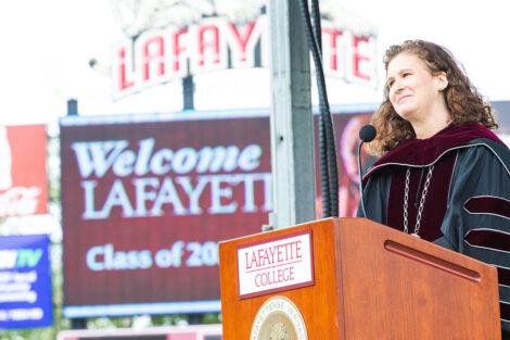 President Nicole Hurd smiles at podium, Fisher Field jumbo-tron says