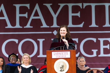 President Nicole Hurd stands at podium and smiles, Lafayette College banner is backdrop