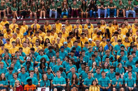 students fill the stands at Fisher Field, they sit in groups with matching red, bule, and green Tshirts