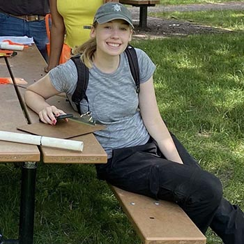 Student sits at picnic table in hat with backpack on while holding clipboard