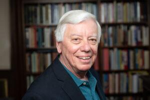 John Kincaid poses in front of bookshelf
