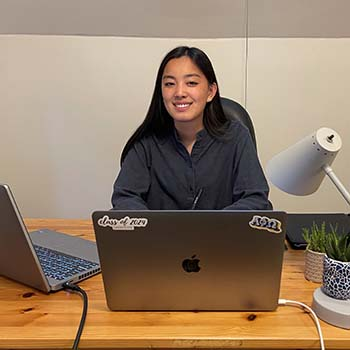 Student sits behind desk with multiple laptops open before her