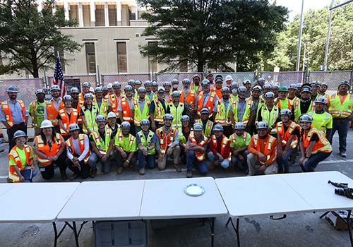 Group of workers in neon shirts at topping out ceremony. Lafayette student is at far left.
