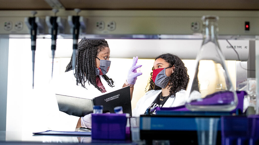 Khadijah Mitchell and Destiny Ortiz Fernandez '22 in masks and lab coats in Rockwell lab