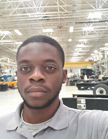 Student takes selfie on production floor with truck parts in background