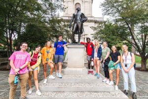 group of students flank the Marquis de Lafayette statue behind Colton Chapel and smile