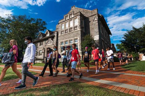 orientation group of new students walk in front of Hogg Hall, sky is a brilliant blue