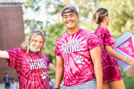 two students in Welcome home tie-dye shirts smile outdoors