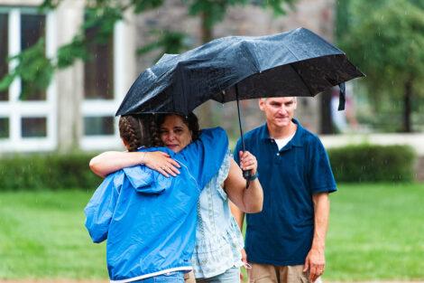 Lafayette student hugs mom holding umbrella goodbye