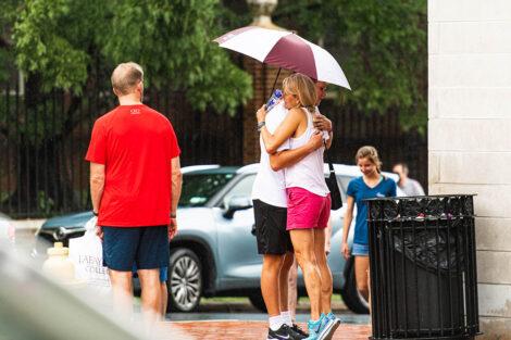Lafayette student holding umbrella hugs mom goodbye