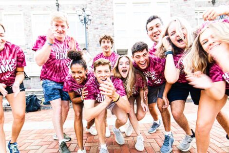 group of students in Welcome home tie-dye shirts smile outdoors