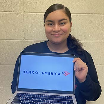 Student holds laptop open with Bank of American logo on the screen