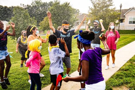 A student celebrates, surrounded by children from the Boys and Girls Club, as water mists around them.