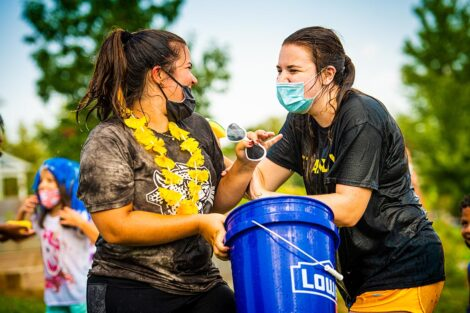 Two students laugh as they fill a bucket with water.
