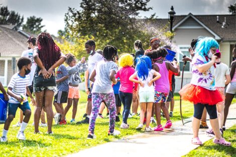 Children from the community and Lafayette students are sprayed with a water hose outside.