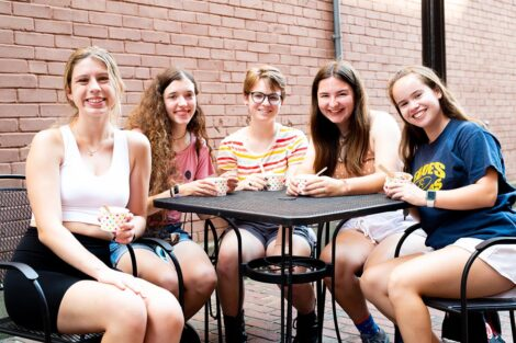 Students smile, sitting at a table in downtown Easton.